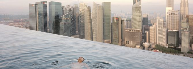 A man floats in the 57th-floor swimming pool of the Marina Bay Sands Hotel, with the skyline of the Singapore financial district behind him. 2013 Paolo Woods & Gabriele GalimbertiÑINSTITUTE