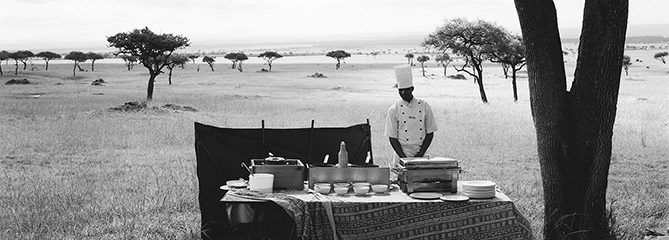 A chef from a nearby luxury lodge waits for his guests to arrive from a hot air balloon excursion before serving them champagne in the middle of the Maasai Mara National Reserve, Kenya.