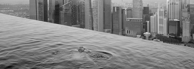 A man floats in the 57th-floor swimming pool of the Marina Bay Sands Hotel, with the skyline of the Singapore financial district behind him.2013Paolo Woods & Gabriele GalimbertiÑINSTITUTE